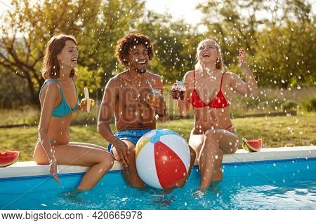 afro-american young man having fun with two caucasian females outdoor in the nature by the pool