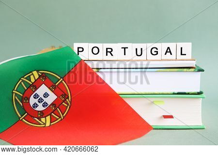 The Inscription Portugal On A Stack Of Textbooks, Books, Exercise Books And National Flag Of Portuga