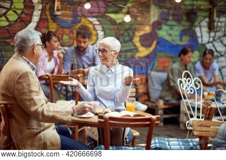 An older couple talking in a relaxed atmosphere in the bar. Leisure, bar, friendship, outdoor
