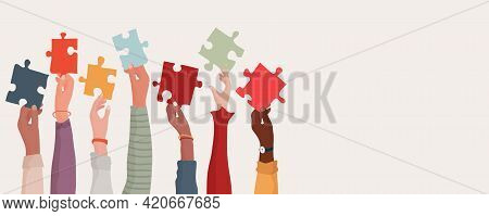 Group Of Multi-ethnic Business People With Raised Arms Holding A Piece Of Jigsaw. Colleagues Of Dive