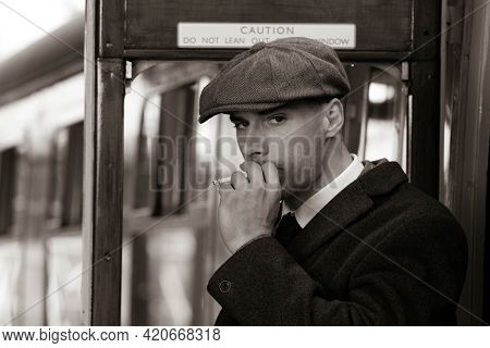 Handsome English Gangster Lighting A Cigarette While Leaving Train At Train Station