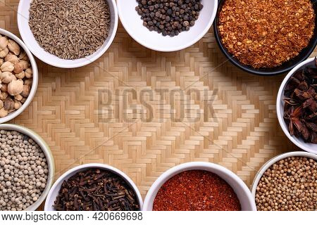 Various Dry Spices And Herbs In A Bowl On Woven Bamboo Background. Asian Food Ingredients (chili, Cl