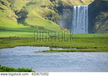 Skogafoss Waterfall, On The Ring Road In Southern Iceland, Is One Of Country's Most Epic Tourist Des