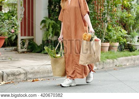 Cropped Image Of Young Woman Carrying Two Bags Full Of Groceries, Bread, Vigetables And Fruits