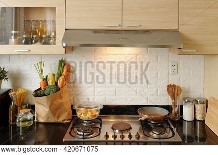 Frying Pan And Saucepan With Pasta On Kitchen Stove And Bag Of Fresh Groceries On Counter