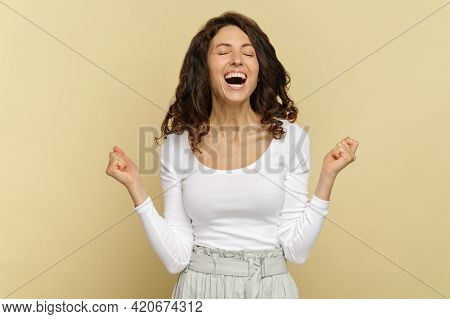 Excited Overjoyed Young Curly Woman Keep Mouth Open With Closed Eyes Hold Fists Up Isolated Over Bei