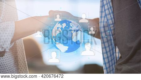 Network of profile icons over globe against mid section of two business people shaking hands. global business and technology concept
