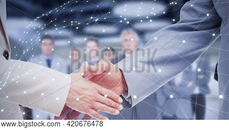Network of connections over two businessmen shaking hands against business people standing. global networking and business technology concept