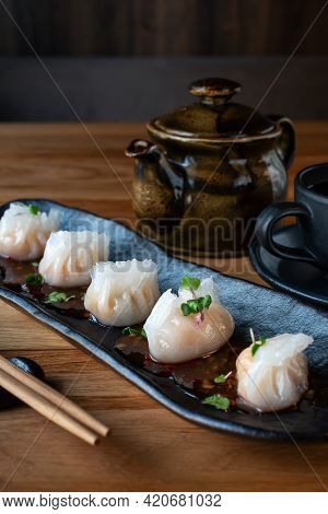 Asian Traditional Dumplings - Dimsum With Shrimp And Bamboo. Steamed Dumplings On Black Plate Near T