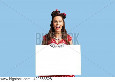 Joyful Pinup Lady In Retro Style Outfit Holding Empty Advertising Board With Free Space On Blue Stud