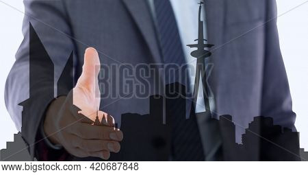 Animation of businessman holding hand over cityscape. business, finance, negotiations and success concept digitally generated image.