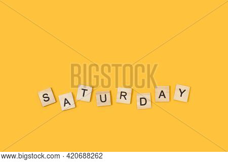 Saturday Write With Wooden Letter Cubes On A Yellow Background