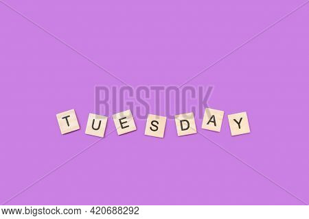 Tuesday Write With Wooden Letter Cubes On A Purple Background