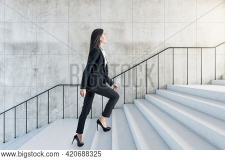 Career Success Concept With Young Woman Climbs The Stairs To The Light In Abstract Building With Sty