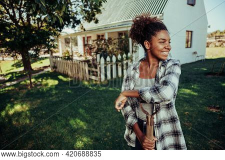 African American Female Standing In Farm Village Leaning On Pitch Fork Smiling In Luscious Green Lan