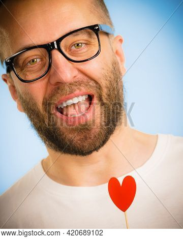 Adult Man Wearing Eyeglasses Being In Love Holding Small Red Shape Heart On Stick. Romance, Flirting
