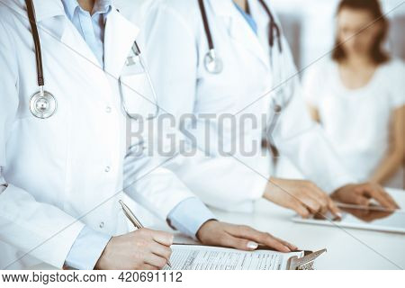 Unknown Woman-doctors At Work With Patient At The Background. Female Physicians Filling Up Medical D