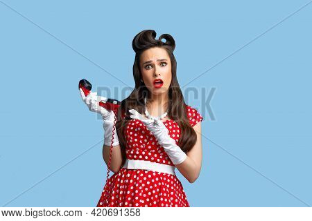 Troubled Young Woman In Retro Style Pinup Dress Pointing At Landline Phone Receiver With Irritation