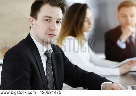 Businessman Headshot At Meeting In Sunny Office. Unknown Entrepreneur Sitting With Colleagues At The