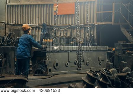 Metallurgical Plant Or Foundry Worker Controls Movement Of Large Steel Product Being Moved By Crane