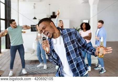 African American Guy With Beer Bottle Singing Karaoke On Home Party With Friends, Singing Songs Into