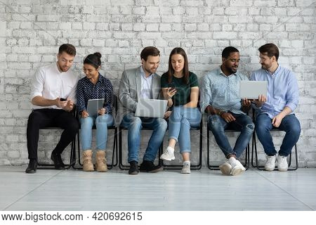 Diverse Couples Of Millennial Gadget Users Sharing Content On Tablet