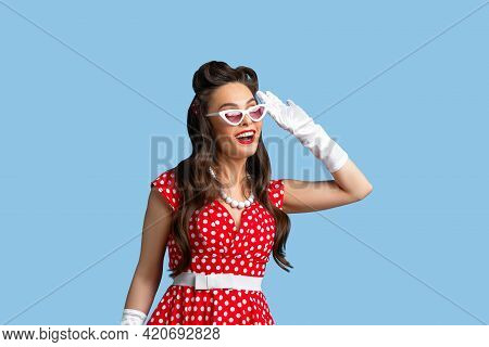 Curious Young Pinup Woman Wearing Retro Dress, Holding Hand Near Ear, Trying To Hear Gossip On Blue