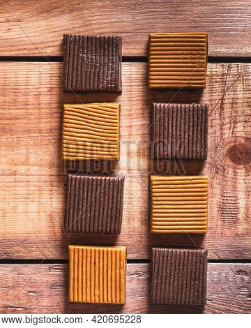 Shrkoladno-creamy Iris Candies Laid Out By Rads On A Wooden Tray Flat Lay