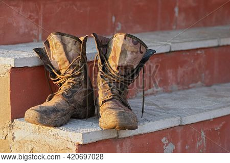 Old And Dirty Military Boots On The Steps Of The Porch. Close Up.