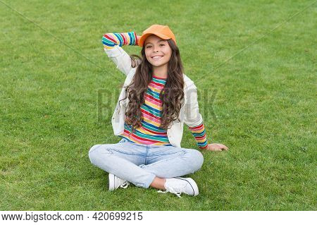 Carefree Days. Happy Child. Female Child Smile Sitting On Green Grass. Childhood And Girlhood