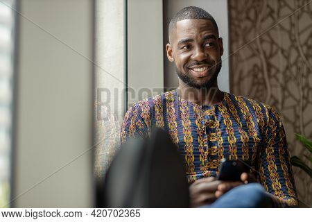Portrait Of Black African Business Man And Entrepreneur Sitting On Window Sill Smiling Looking Into