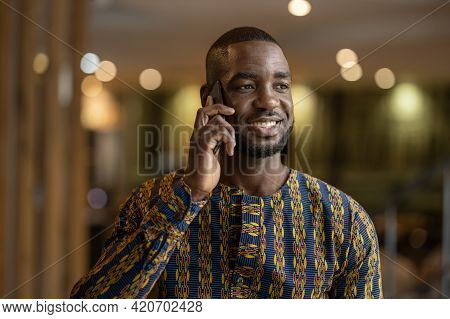 Black African Businessman And Entrepreneur Using Mobile Smart Phone. Smiling And Wearing Traditional