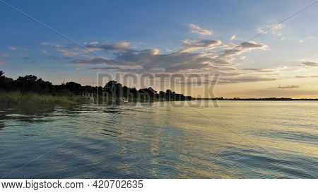 Zambezi River At Sunset. The Clouds In The Blue Sky Are Highlighted In Orange. Reflection On The Sur