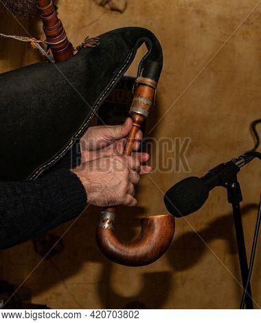 The Musician Holds A Bagpipe In His Hands. Playing A Musical Instrument - Bagpipes. Close-up.
