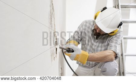 House Renovation Concept, Construction Worker Breaks The Old Plaster Of The Wall With Pneumatic Air