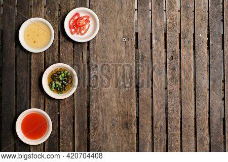 Flavoring Food On Wooden Background At Restaurant.