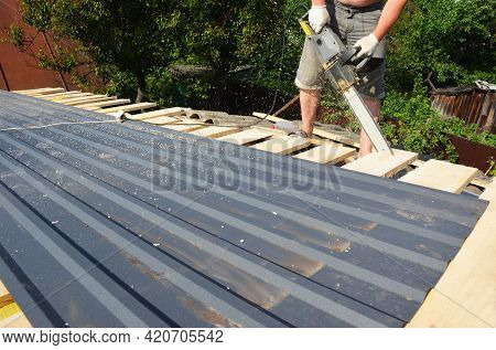 Roofing Construction: A Roofer Is Cutting With An Electric Saw Roof Sheathing Boards Making The Roof