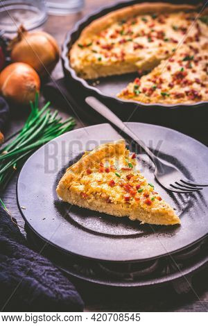 Piece of homemade onion tart or pie with bacon and chive on wooden background