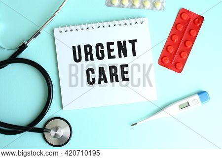 The Text Urgent Care Is Written On A White Notepad That Lies Next To The Stethoscope And Pills On A
