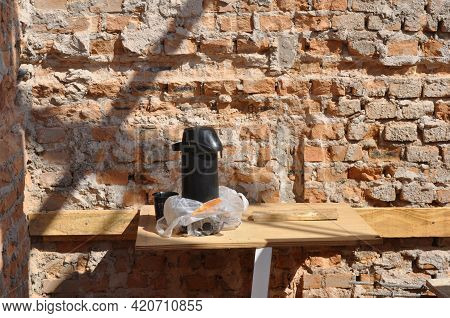 Bottle. Coffee bottle on top of wooden boards under construction, in the background, masonry wall being completed, Brazil, South America