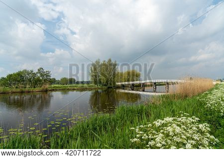 White Wooden Bridge Across A Calm Canal In Country Landscape