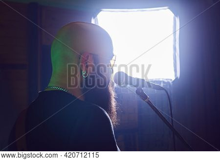 Man musician playing guitar and singing. Portrait of rock and roll musician on green background. Musician playing music. Rock music musician singing on microphone.