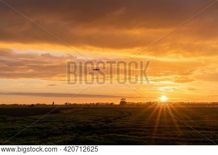 Drone Flying Over Green Springtime Meadows With A Colorful Orange Sunset Sky Behind