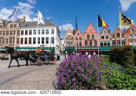 Tourists Enjoy An Idyllic Horse And Carriage City Tour In The Historic Old Town Of Brugge