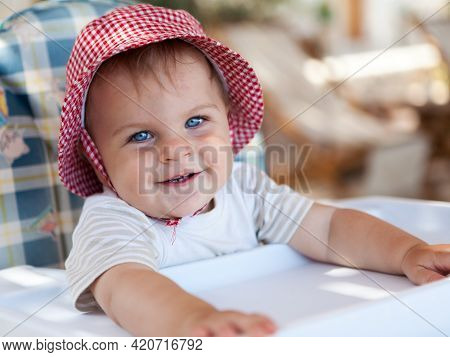 Little Cute Smiling Girl In A Hat Sitting In A Baby Feeding Chair, Looking Straight Into The Camera