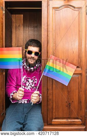 Bearded Gay Man Sitting Inside A Closet, Smiling With Sunglasses And Rainbow Lgbt Pride Flags. Verti