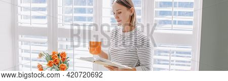 Beautiful Happy Middle Age Woman Reading Book At Home. Young Woman With Short Hair Drinking Tea Coff