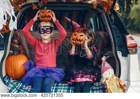 Trick Or Trunk. Children Siblings Sisters Celebrating Halloween In Trunk Of Car. Friends Kids Girls