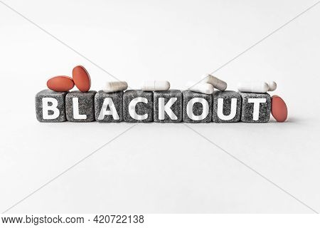 Blackout The Word On Stone Cubes. Cubes Stand On A White Surface, Many White And Red Pills. Medicine
