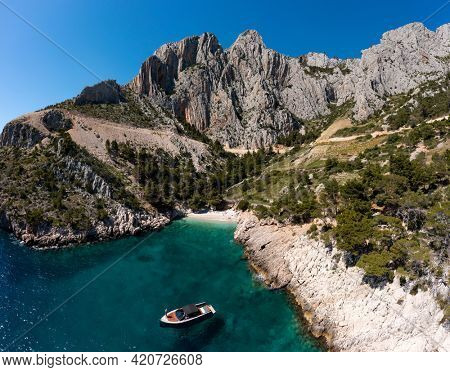 Beautiful bay with mountains, turquoise water and boat in Croatia, Hvar island. Tourism, vacation, travel, boat trip.